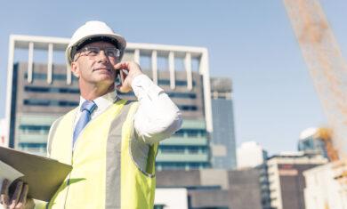 Senior engineer man in suit and helmet talking mobile phone